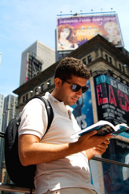 Photo of a traveler reading a Lonely Plant guide book in New York City